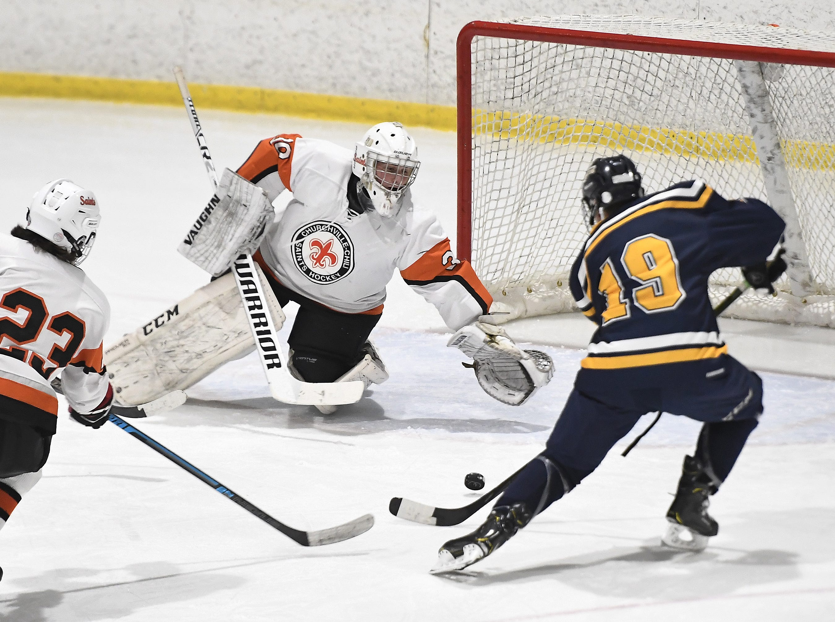 Webster Thomas' Tommy Ammon (19) puts the puck past Churchville-Chili goalie Ethan Breton for the Titans' third goal during a regular season game played at the Scottsville Ice Arena, Tuesday, Jan. 22, 2019. Webster Thomas beat Chuchville-Chili 4-1.