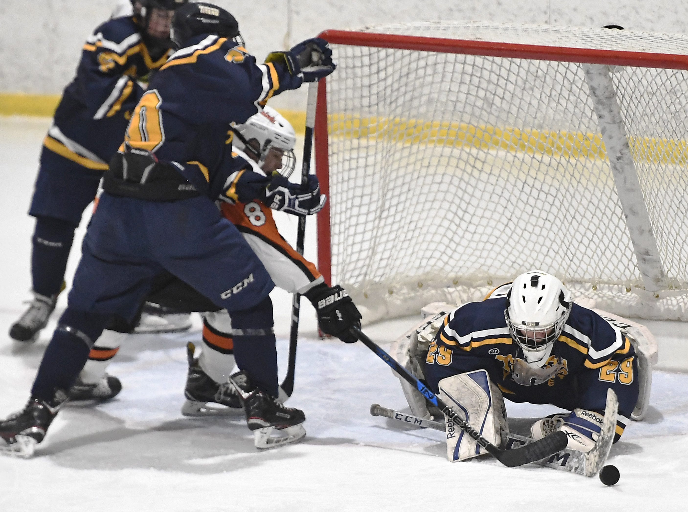 Webster Thomas goalie Cody Rougeux, right, pokes the puck away as Matthew Stuewe shields  Churchville-Chili's Dylan Clark off the play during a regular season game played at the Scottsville Ice Arena, Tuesday, Jan. 22, 2019. Webster Thomas beat Chuchville-Chili 4-1.
