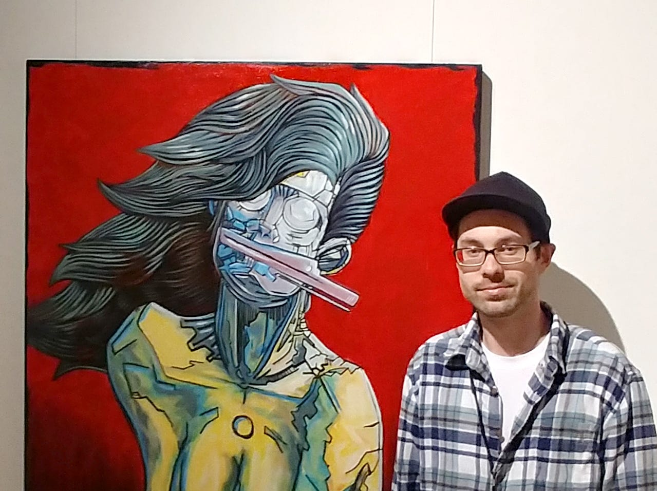 Artist Justin Patton stands with one of his paintings.Patton has work  exhibited at Redding's Old City Hall during the 2019 Cultural Cruise.