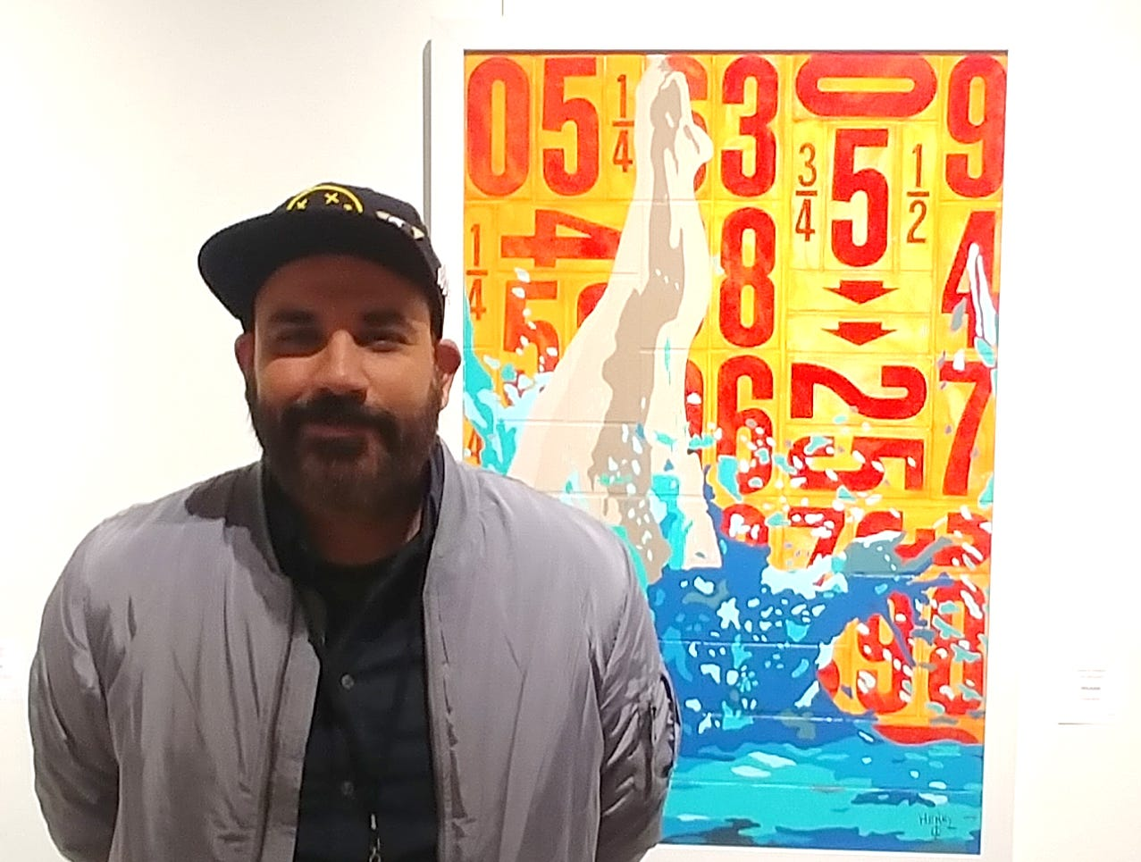 Artist Karlo Henry Velazquez stands with one of his paintings. Velazquez has work  exhibited at Redding's Old City Hall during the 2019 Cultural Cruise.