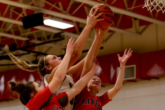 Kennedy's Sophia Carley (00) grabs a rebound between Santiam's Came Duncan (32) and Maddy White (14) in the Santiam vs. Kennedy girls basketball game at Kennedy High School in Mt. Angel on Tuesday, Jan. 22, 2019. Kennedy won the gam 62-49.