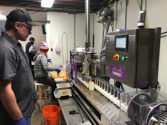 Dewey Beer Co. head brewer Michael Reilly watches the canning machine to make sure things run smoothly, while the rest of the team works the assembly line.