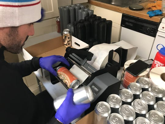 Dewey Beer Co. co-owner Brandon Smith applies a label to a can of Peanut Butter Blossom stout.