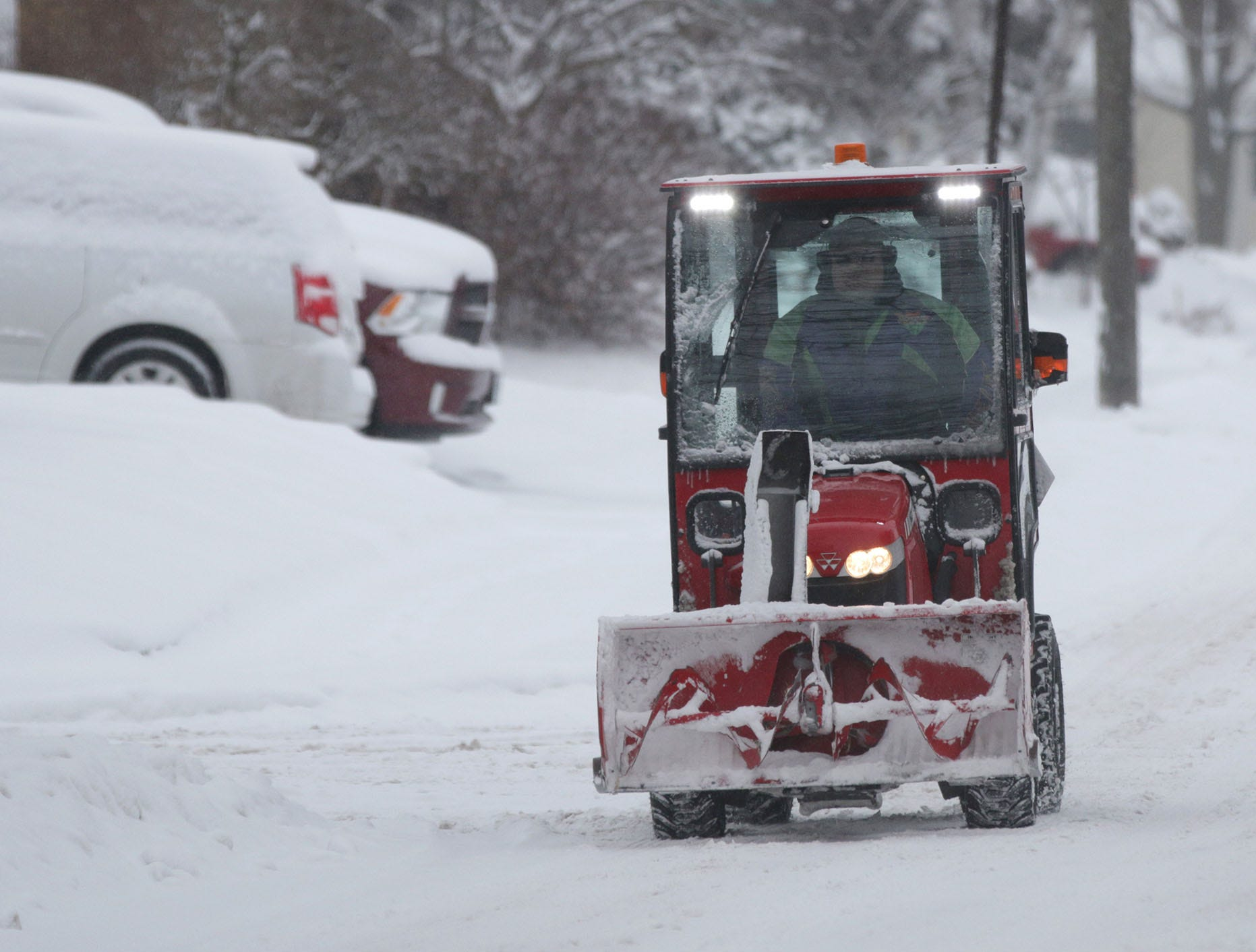 A man drives a covered snow blower down Ashland Avenue, Wednesday, January 23, 2019, in Sheboygan, Wis.