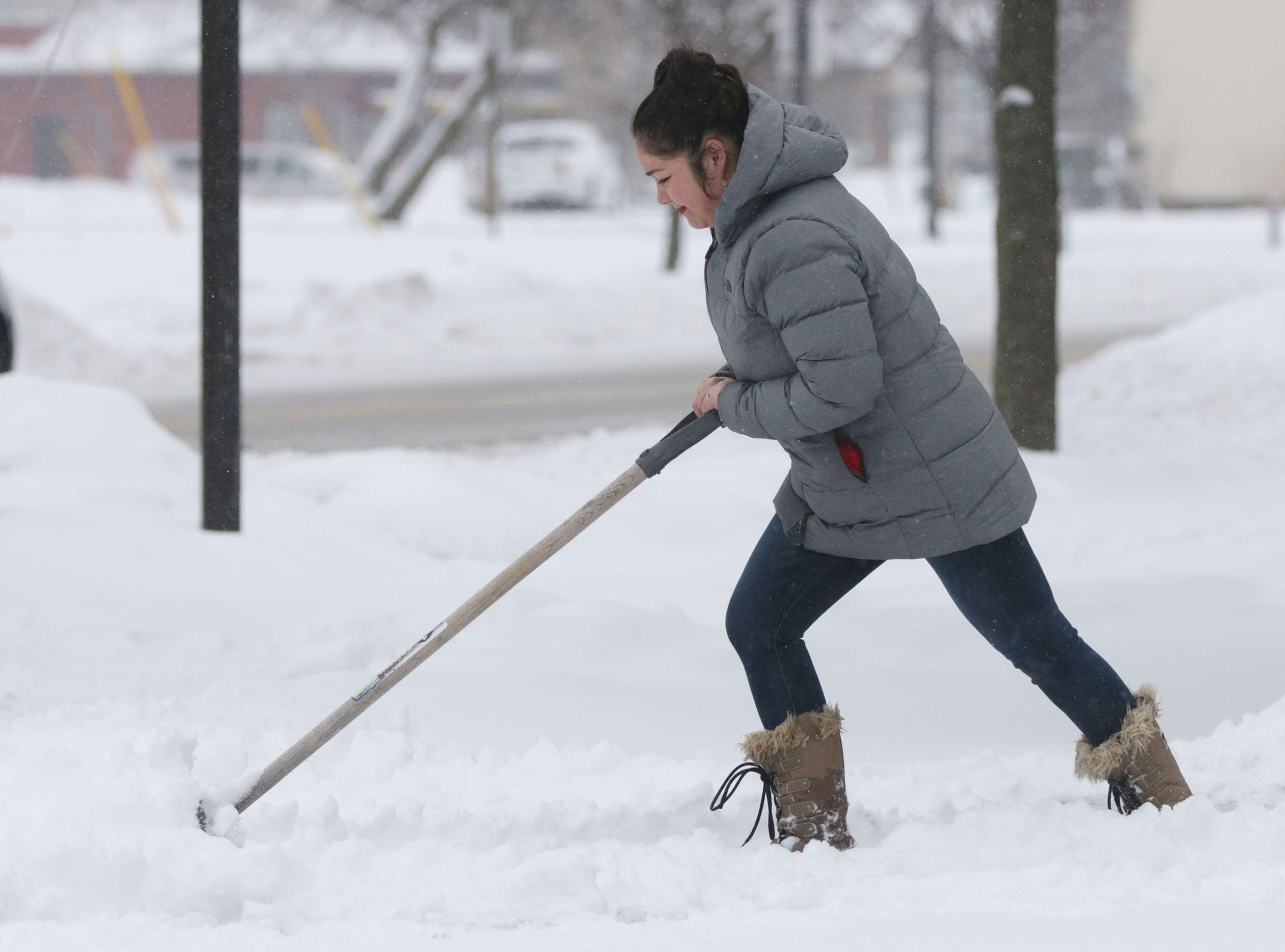 Rieyna Guerrerro pushes a snow shovel at  La Reyna on Indiana Avenue, Wednesday, January 23, 2019, in Sheboygan, Wis.