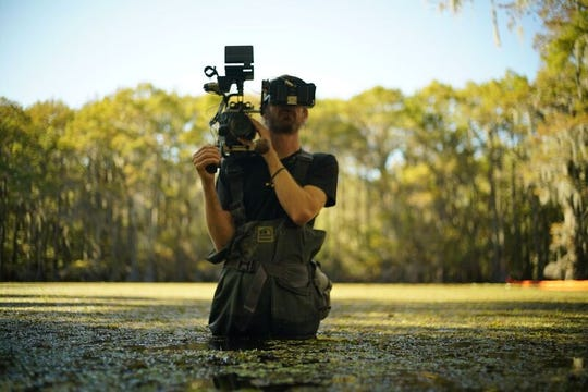 """A photographer works on the National Geographic's series """"Explorer"""" while filming on Caddo Lake."""