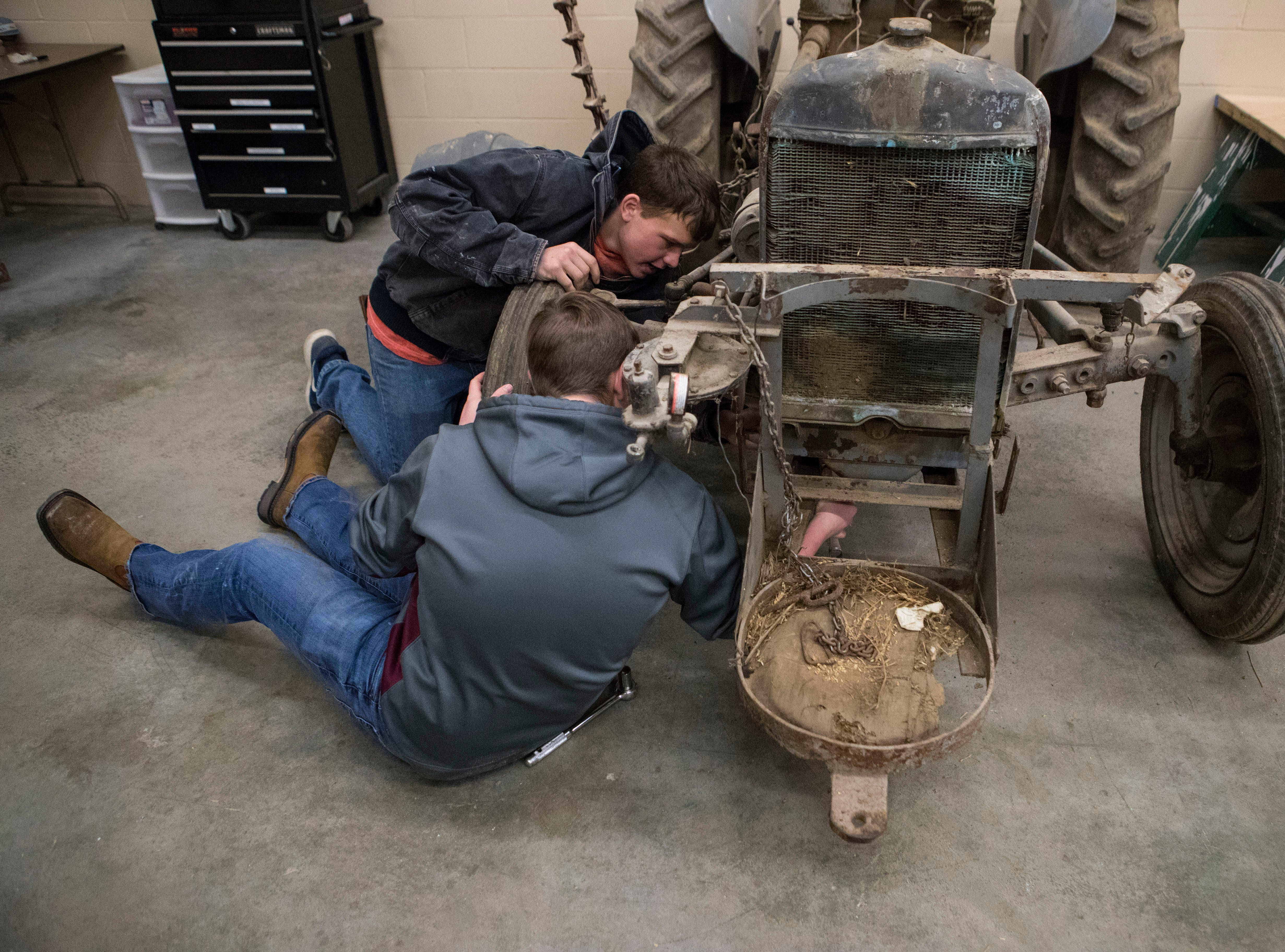 Jackson Klemme, 18, and Mitchell Healy, 18, repair a tractor during agriculture mechanics class at Harrisburg High School, Wednesday, Jan. 23, 2019 in Harrisburg, S.D.