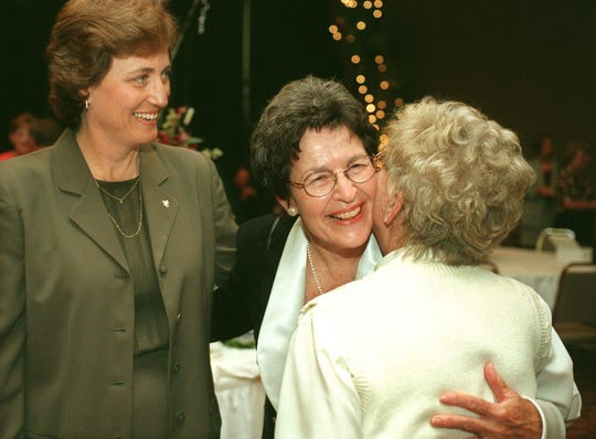 Mary Jo Wynn, center, receives a congratulatory hug from friend Bee Payne-Stewart while Linda Dollar, left, looks on at Wynn's retirement reception party at University Plaza Convention Center in 1998.