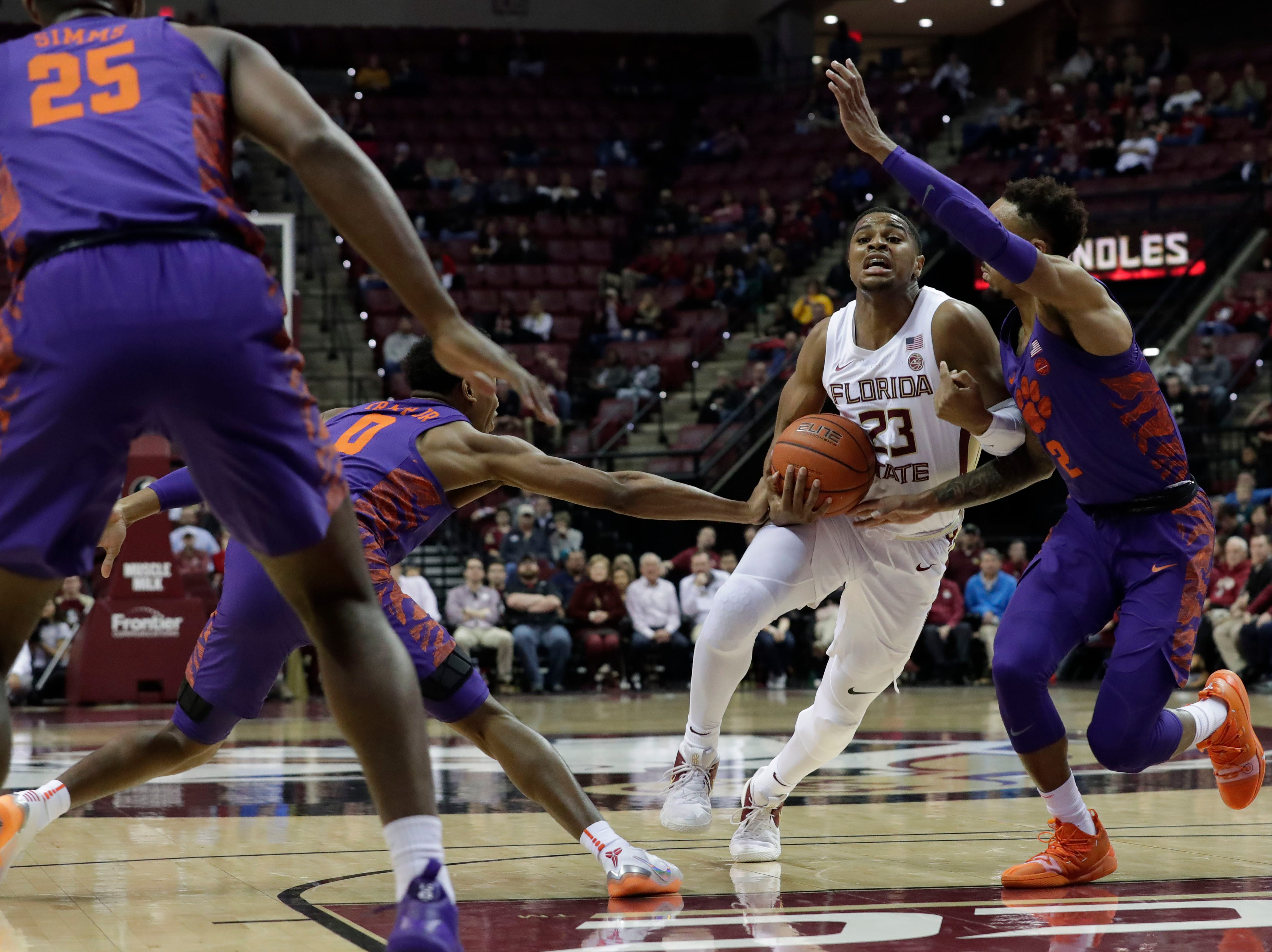 Florida State Seminoles guard M.J. Walker (23) drives the ball to the hoop between two defenders. The Florida State Seminoles face off against the Clemson Tigers at the Tucker Civic Center, Tuesday, Jan. 22, 2019.
