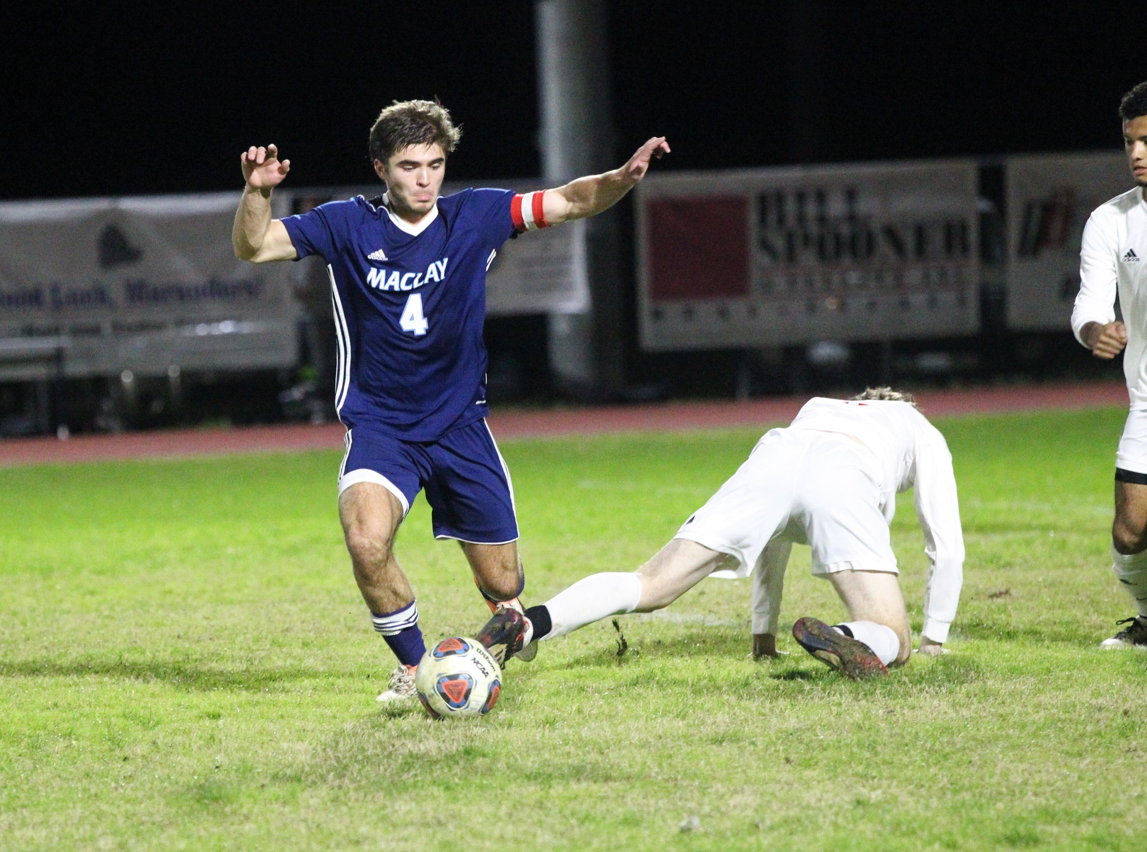 Maclay's Jordan Pichard has a ball poked away by Leon's Nick Ramsden and gets tripped as Leon's boys soccer team beat Maclay 3-1 on Jan. 22, 2019.