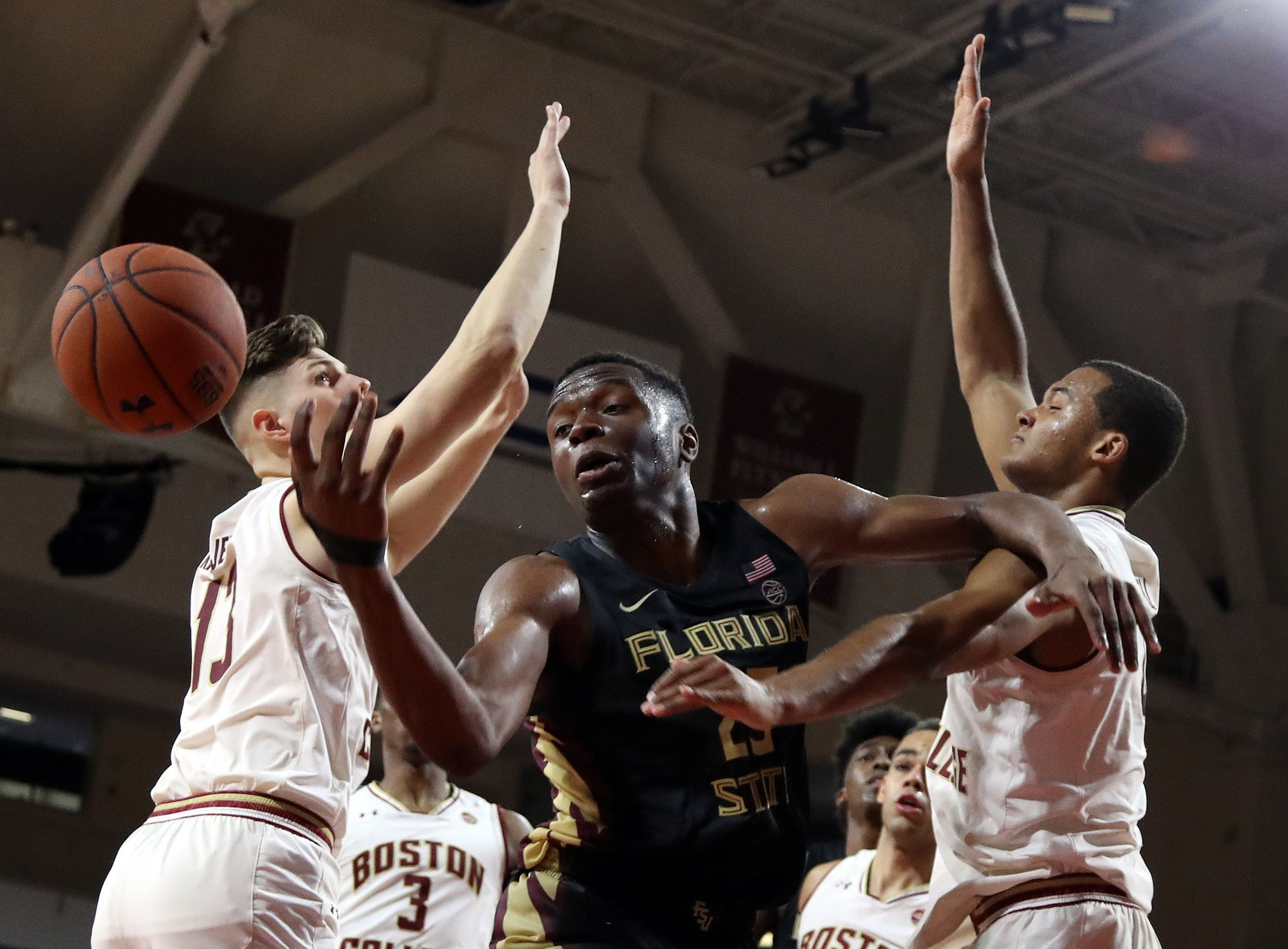 Jan 20, 2019; Chestnut Hill, MA, USA; Florida State Seminoles forward Mfiondu Kabengele (25) looses the ball defended by Boston College Eagles forward Luka Kraljevic (13) and Boston College Eagles forward Steffon Mitchell (41) during the second half at Conte Forum. Mandatory Credit: Paul Rutherford-USA TODAY Sports