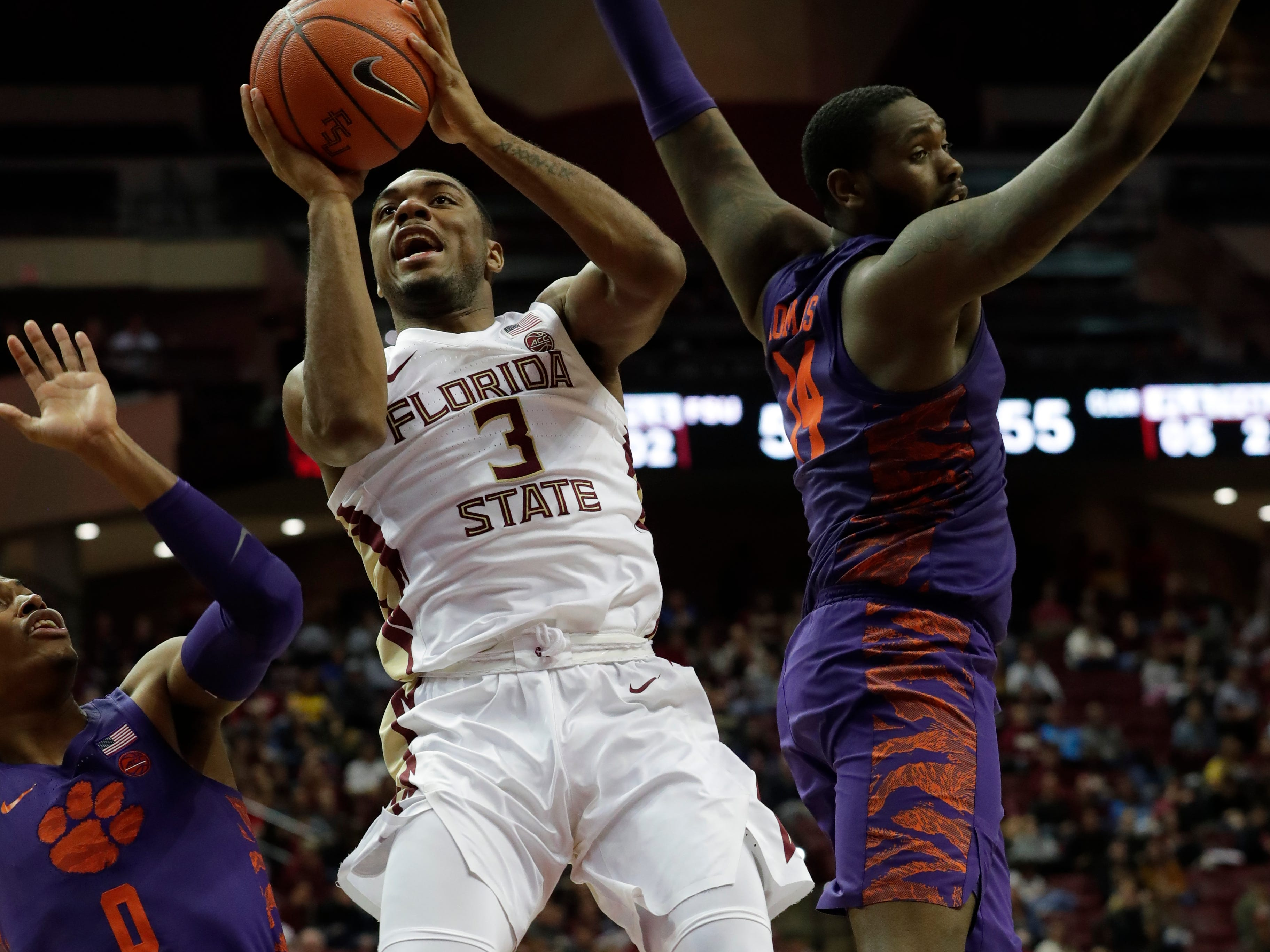 Florida State Seminoles guard Trent Forrest (3) shoots from inside the paint with Clemson Tigers guard Clyde Trapp (0) and Clemson Tigers forward Elijah Thomas (14) guarding him. The Florida State Seminoles face off against the Clemson Tigers at the Tucker Civic Center, Tuesday, Jan. 22, 2019.