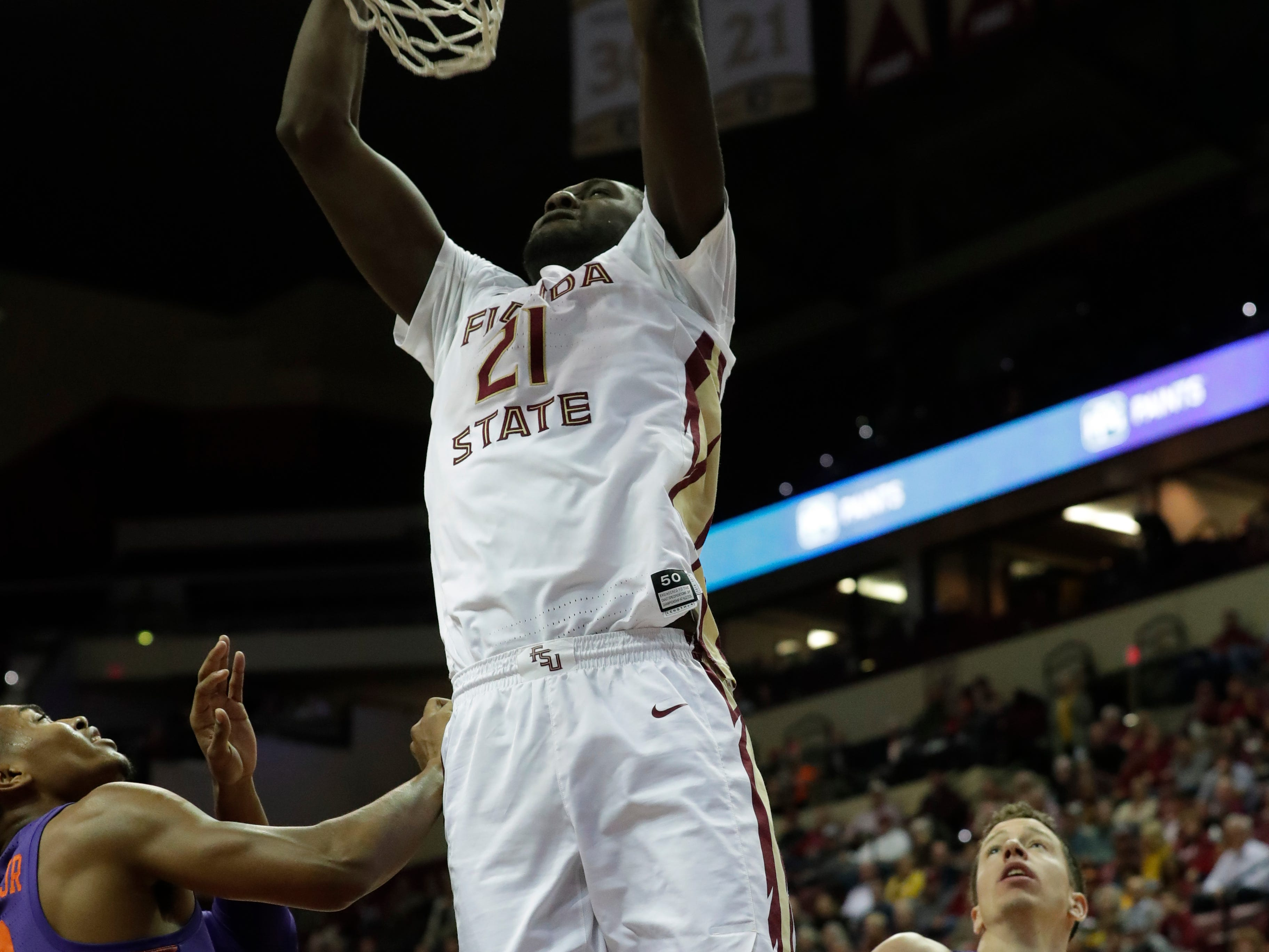 Florida State Seminoles center Christ Koumadje (21) dunks the ball on a defender. The Florida State Seminoles face off against the Clemson Tigers at the Tucker Civic Center, Tuesday, Jan. 22, 2019.
