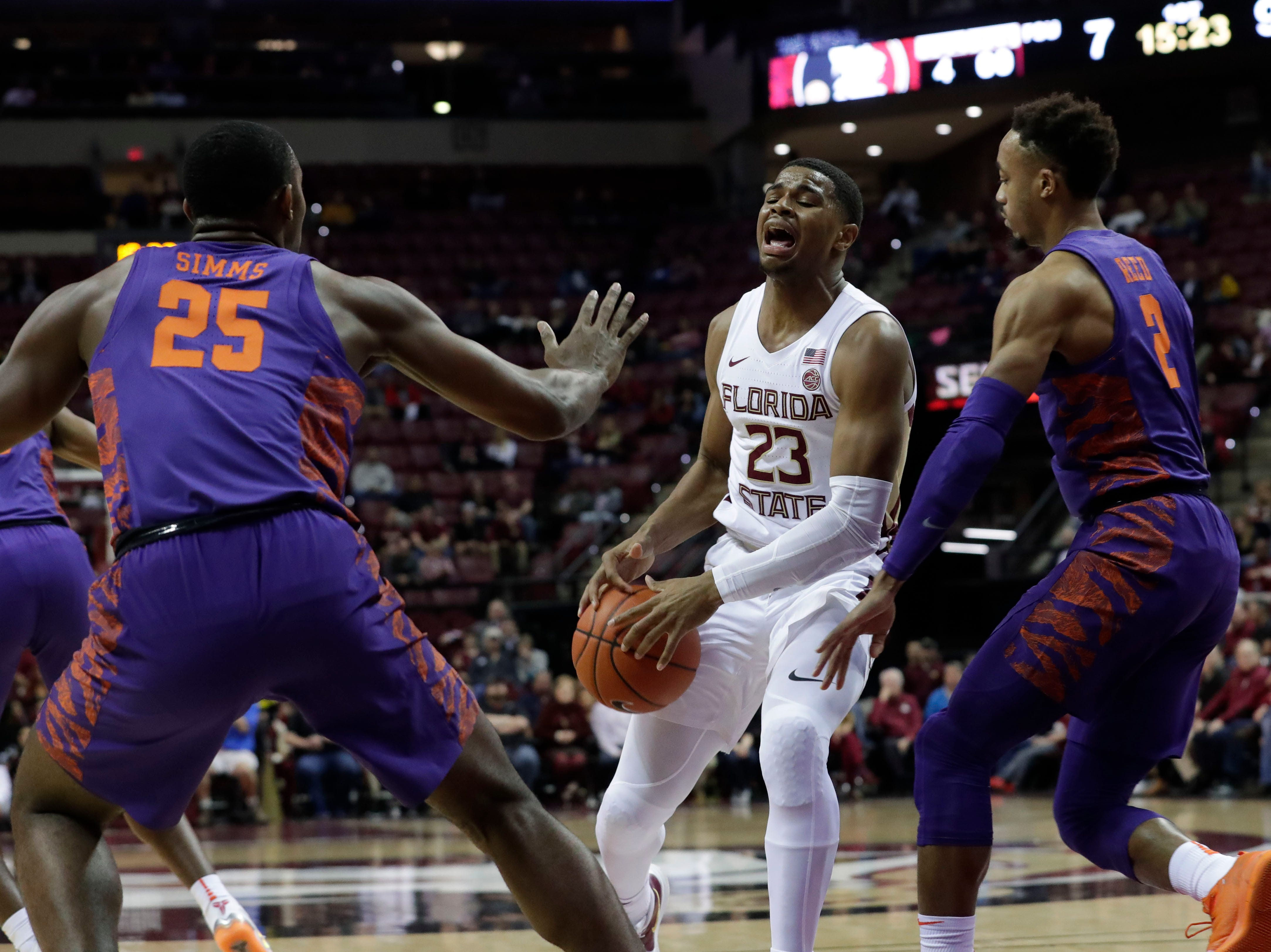 Florida State Seminoles guard M.J. Walker (23) tries to keep ahold of the ball as he fights his way through Clemson Tigers forward Aamir Simms (25) and Clemson Tigers guard Marcquise Reed (2). The Florida State Seminoles face off against the Clemson Tigers at the Tucker Civic Center, Tuesday, Jan. 22, 2019.