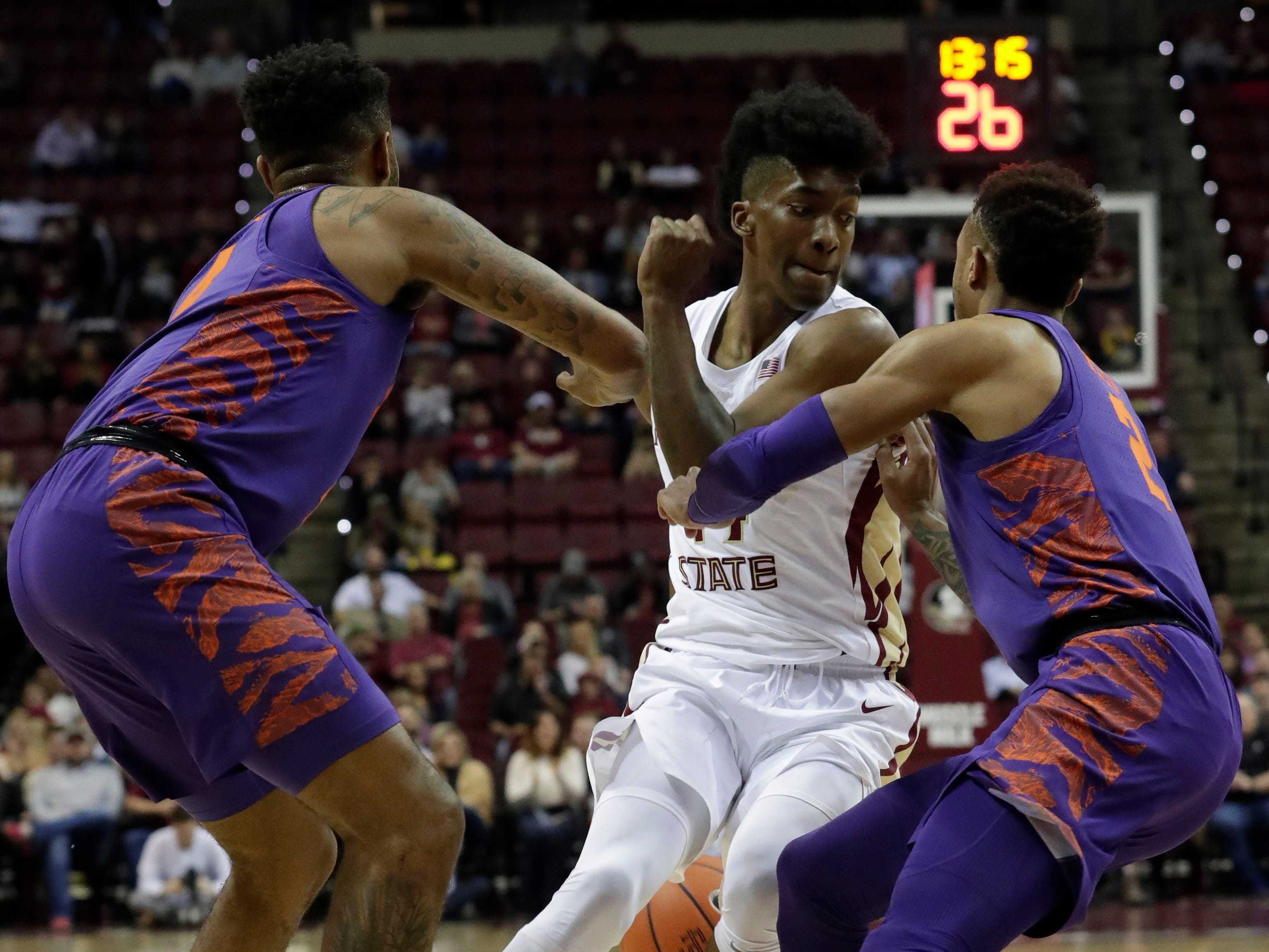 Florida State Seminoles guard Terance Mann (14) dribbles the ball behind his back while fighting off two defenders. The Florida State Seminoles face off against the Clemson Tigers at the Tucker Civic Center, Tuesday, Jan. 22, 2019.