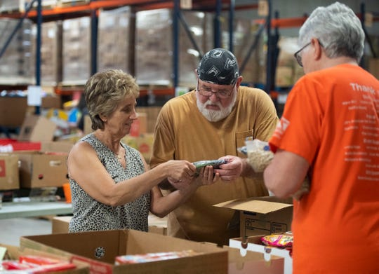 Volunteers (from left) Elaine Taylor, a seasonal resident of North Hutchinson Island, Michael Cool, of Fort Pierce, and Dickie Brooks, of Fort Pierce, spent their morning packing food boxes for furloughed federal employees Wednesday, Jan. 23, 2019, at the Treasure Coast Food Bank in Fort Pierce. The food bank is offering boxes of food, hygiene products, cleaning products and pet food to out of work federal employees. The organization is hosting another sorting and packing event Feb. 2. To volunteer, call the Treasure Coast Food Bank at 772-489-3034.