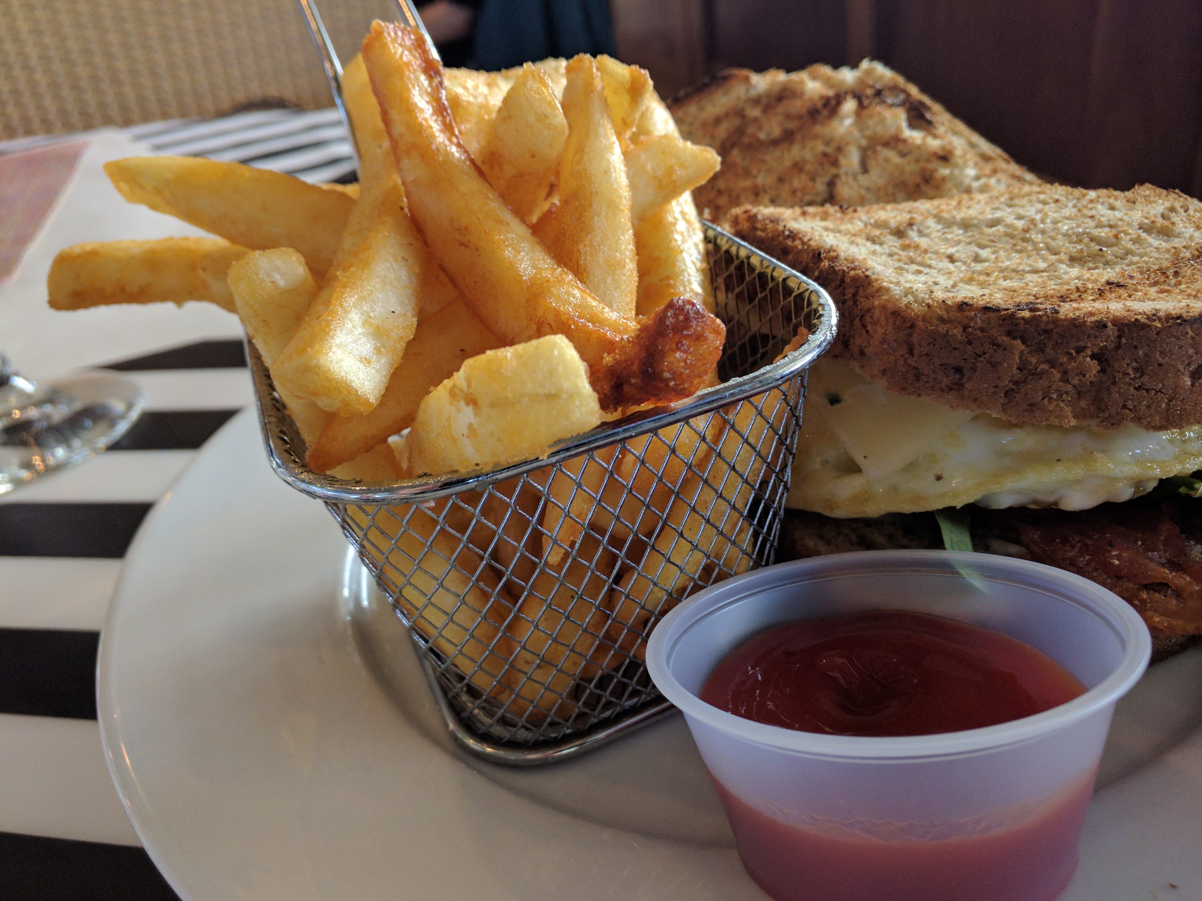"""The tall """"eggwich"""" is loaded with goodies and served with crispy French fries at Counter Culture in Vero Beach."""