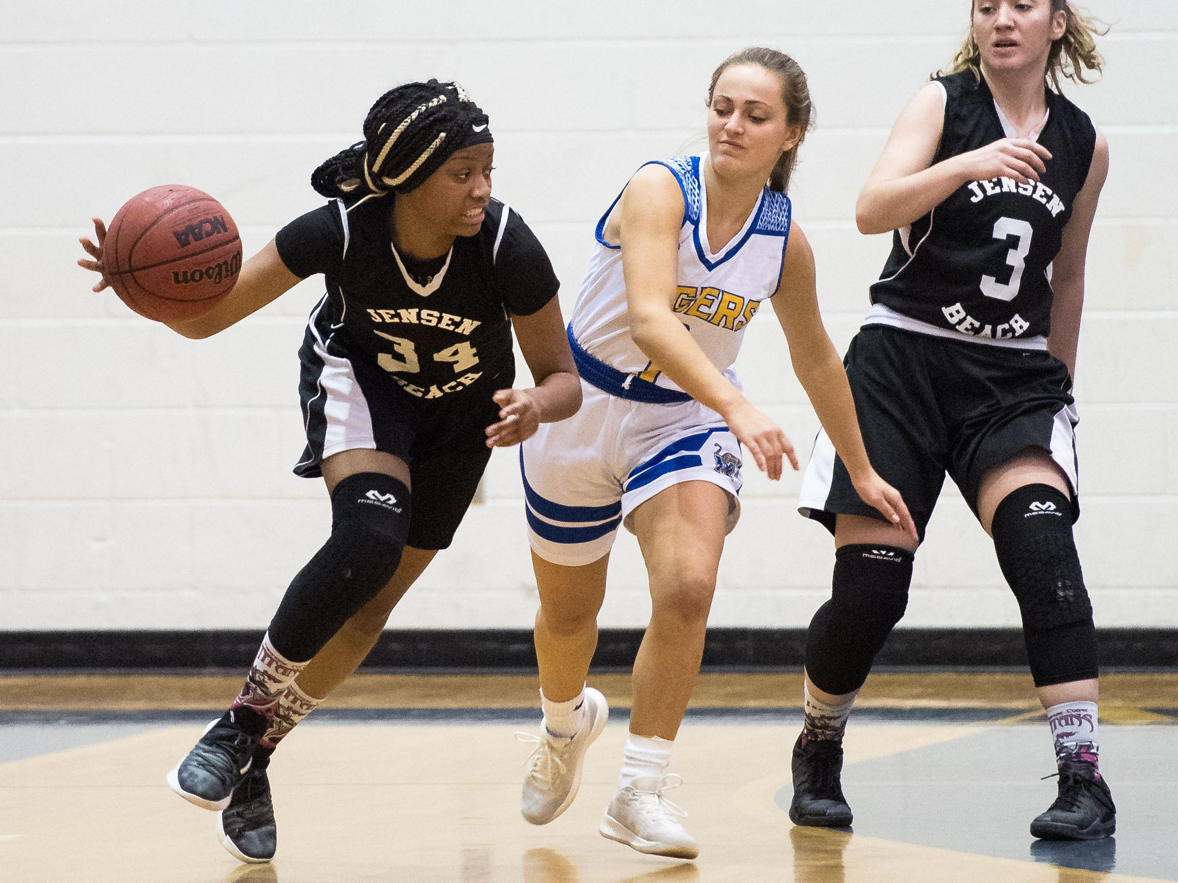 Jensen Beach's Jacqmea Britt tries to keep the ball away from Martin County's Allison Daniel (center), as Jensen teammate Hope Donow tries to help at right, during the third period of the high school girls basketball game Tuesday, Jan. 22, 2019, at Martin County High School in Stuart.