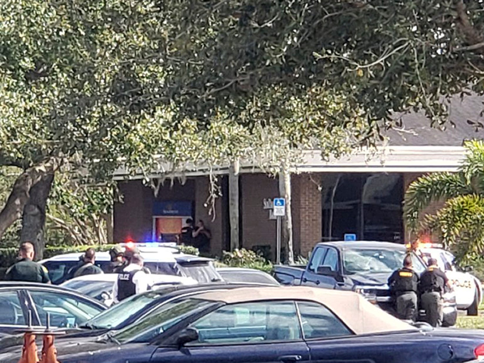 Law enforcement officials take cover outside a SunTrust Bank branch, Wednesday, Jan. 23, 2019, in Sebring, Fla.