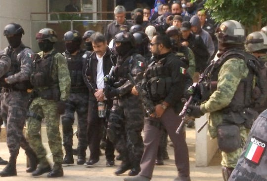 "In this May 2, 2017, file photo, Damaso Lopez Nuñez, a leader in Mexico's Sinaloa drug cartel, is escorted by police after his capture at an upscale apartment building in Mexico City. Lopez testified Wednesday, Jan. 23, 2019, at the U.S. trial of the Mexican drug lord known as ""El Chapo,"" implicating kingpin Joaquin Guzman's wife, Emma Coronel Aispuro, in his 2015 prison escape."