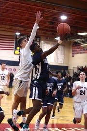 Poughkeepsie High School's  Jamik Carter fights through the Byram Hills defense for a layup on Jan. 22.