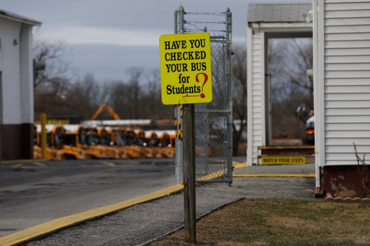 A sign at the Red Clay School District bus yard near New Castle reminds drivers to check for kids.