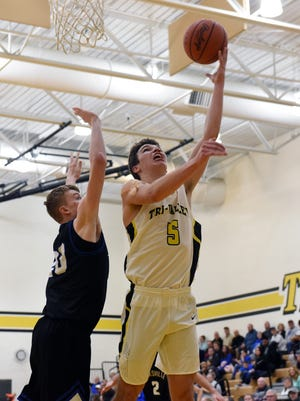 Tri-Valley's Keaton Williams goes up for a layup over Zanesville's Brennan Reasoner during the Scotties' 54-38 win on Tuesday night in Dresden. Williams scored a game-high 23 points.