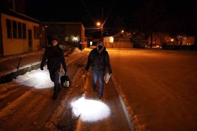 Zane State College Criminal Justice majors Austin Wheeler and Emily Coakley carry supplies for the homeless down an alley in downtown Zanesville during the annual homeless county Tuesday night.