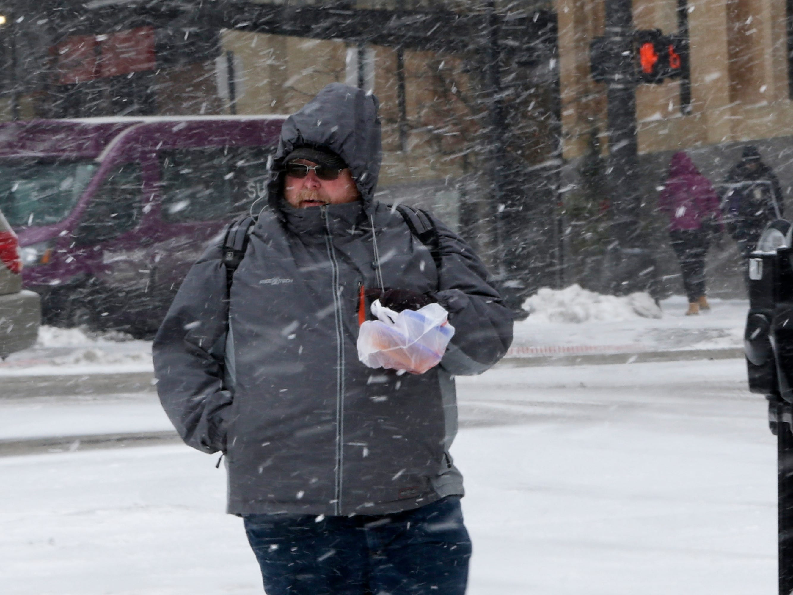 A person walks in the blowing snow in Omaha, Neb. Snow and freezing rain has prompted officials to close the largest school districts in Nebraska and Iowa ahead of a winter storm that's threatening the Midwest with several inches of snow.