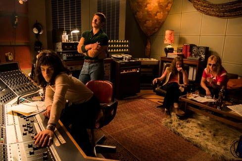 "Queen singer Freddie Mercury (Rami Malek, far left) futzes with the knobs of a studio mixing desk in ""Bohemian Rhapsody."""