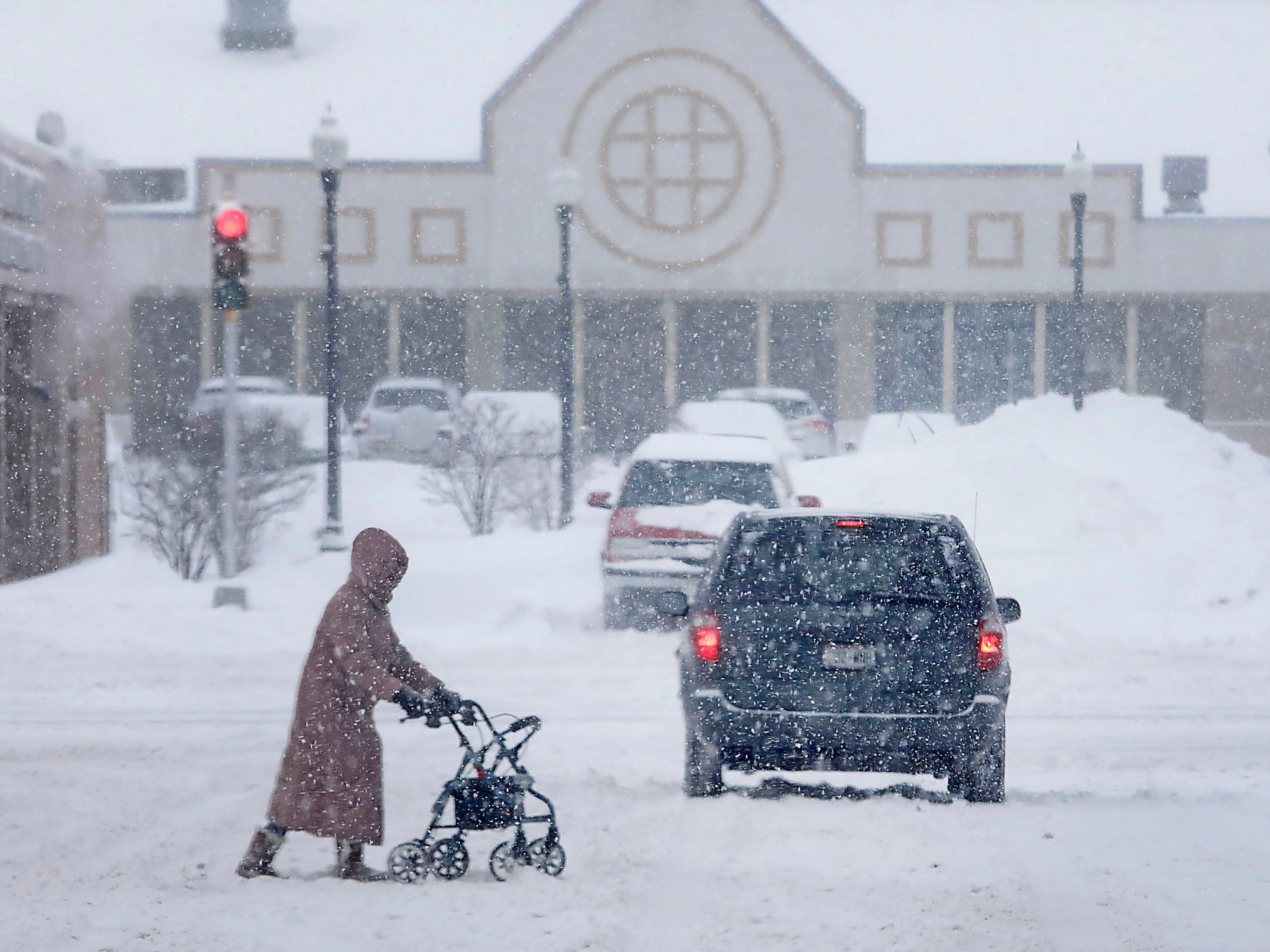 As a winter storm system moves through the upper Midwest, a pedestrian makes her way through the slippery, snowy conditions in Madison, Wis.  Jan. 23, 2019.