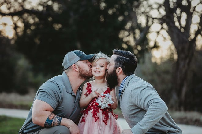 David Lewis and Dylan Lenox share a kiss with daughter, Willow, before she heads to a daddy-daughter dance.