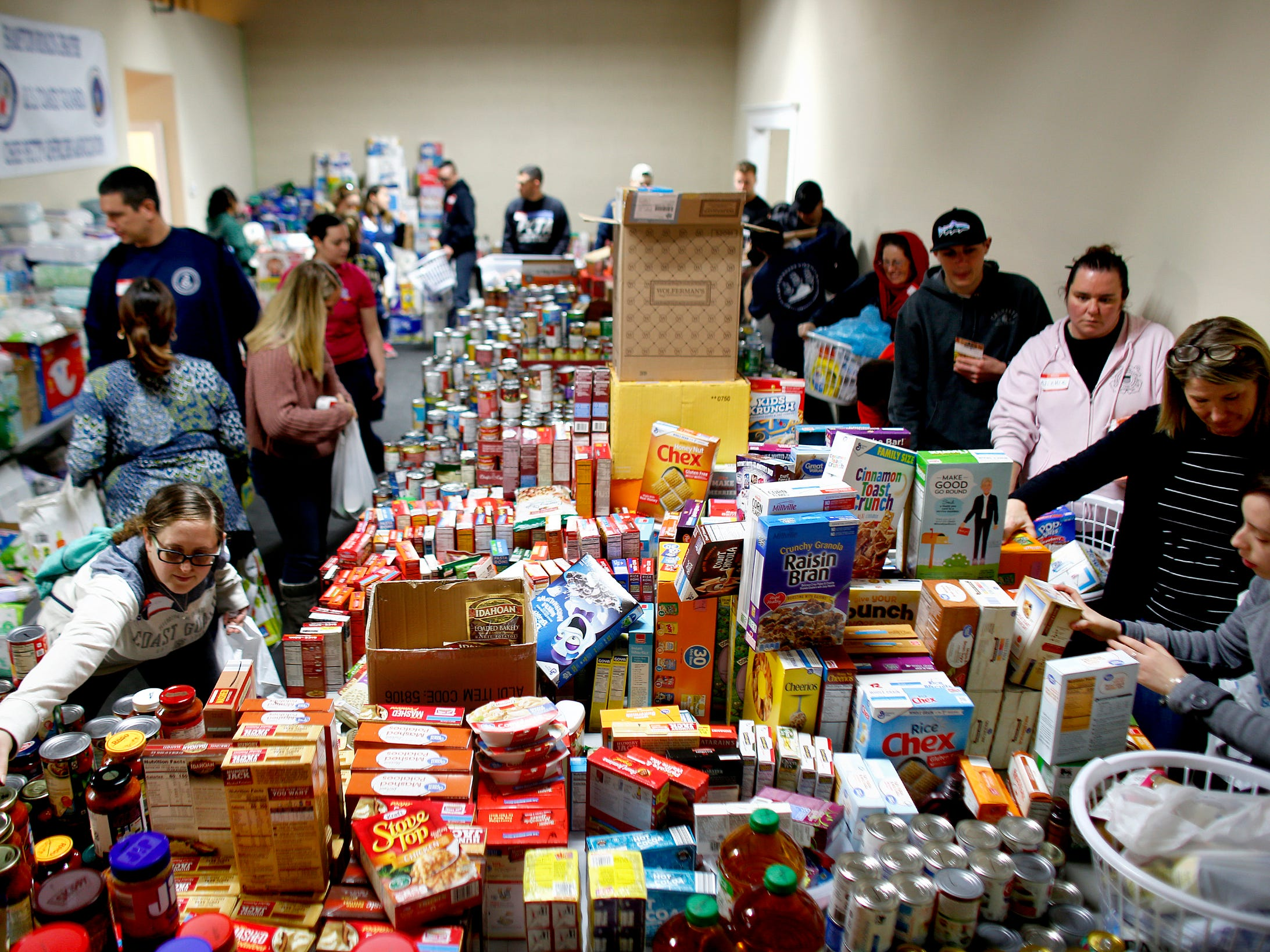 Hundreds of volunteers and recipients Saturday, Jan. 19, 2019 at Help for Hampton Roads Coast Guard Families food drive, sponsored by the Chief Petty Officer Association, in Chesapeake for families affected by the shutdown. (Stephen M. Katz/The Virginian-Pilot via AP) ORG XMIT: VANOV102