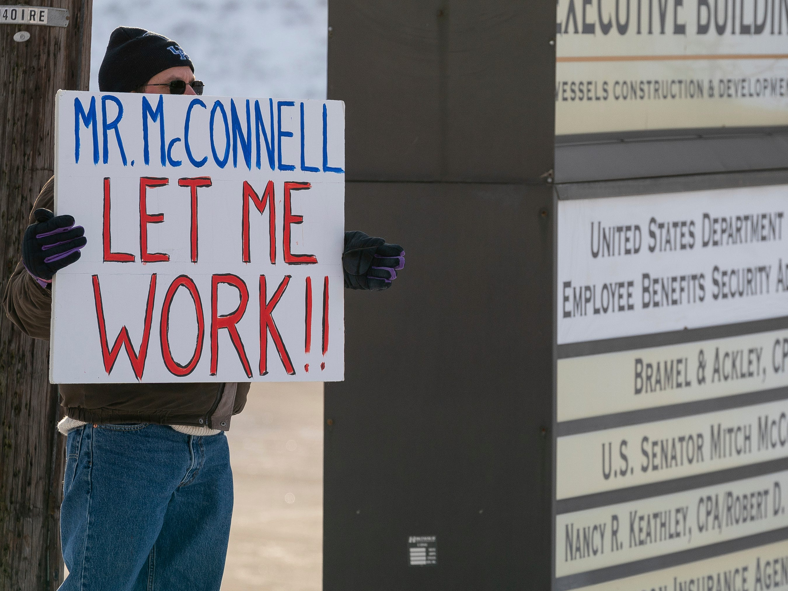 Furloughed EPA worker Jeff Herrema holds a sign outside the offices of U.S. Senator Mitch McConnell, in Park Hills, Ky., Tuesday, Jan 22, 2019. (AP Photo/Bryan Woolston) ORG XMIT: KYBW109
