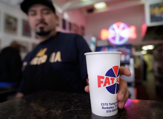 Fat Slice pizza employee Gustavo Munoz places a disposable cup on a table Wednesday, Jan. 23, 2019, in Berkeley, California. Berkeley has approved a 25-cent tax on disposable cups city officials say is part of an effort to eliminate restaurant waste.