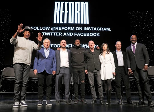 "Entrepreneur ad recording artist Shawn ""Jay-Z"" Carter, from left, gestures as he poses with New England Patriots owner Robert Kraft, Philadelphia 76ers co-owner and Fanatics executive chairman Michael Rubin, recording artist Meek Mill, Galaxy Digital CEO and founder Michael Novogratz, Brooklyn Nets co-owner Clara Wu Tsai, Third Point CEO and founder Daniel S. Loeb, and REFORM Alliance CEO and political activist Van Jones after the group announced a partnership to transform the American criminal justice system, Wednesday, Jan. 23, 2019, in New York."