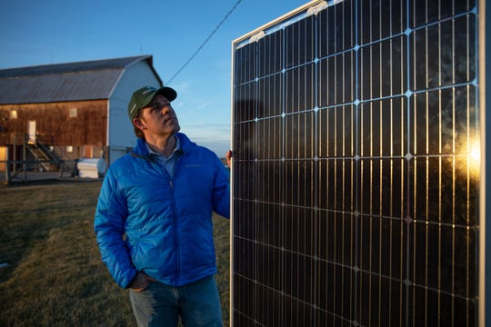 Dan Litchfield, Invenergy's renewable energy manager, shows a solar panel outside of the company's office in Cobb. These panels would become part of a 3,500-acre solar project, one of the largest solar farms on cropland in the nation.