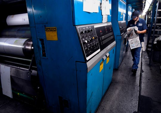 Press operator Tony Silva studies the print quality of a copy of the San Angelo Standard-Times as it was being published Wednesday at the Abilene Reporter-News.