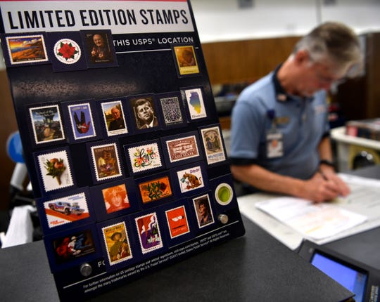 Examples of Forever stamps are displayed on a counter next to Jerry Pullin as he assists a customer Thursday at the post office in Abilene. The price of first class postage for a letter will increase Sunday to 55 cents. Forever stamps purchased before then will continue to be honored.