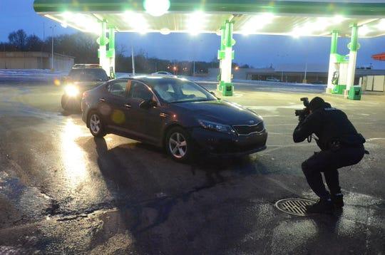 Corporal Andrew Olsen photographs the car involved in a pedestrian crash Thursday morning.