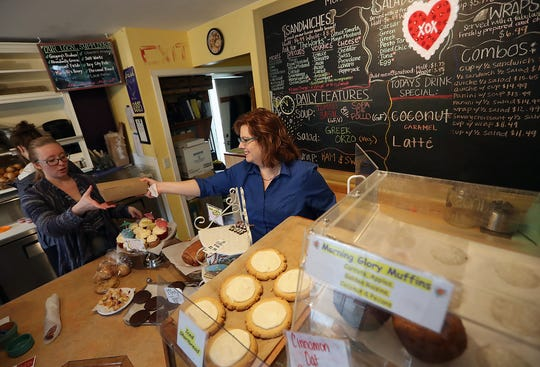 Monica Downen hands a box of pastries to Amanda Carmen (left) as they fill serve up baked goods and sandwiches from behind the counter at Monica's Waterfront Bakery & Cafe in Silverdale on Thursday, January 24, 2019.