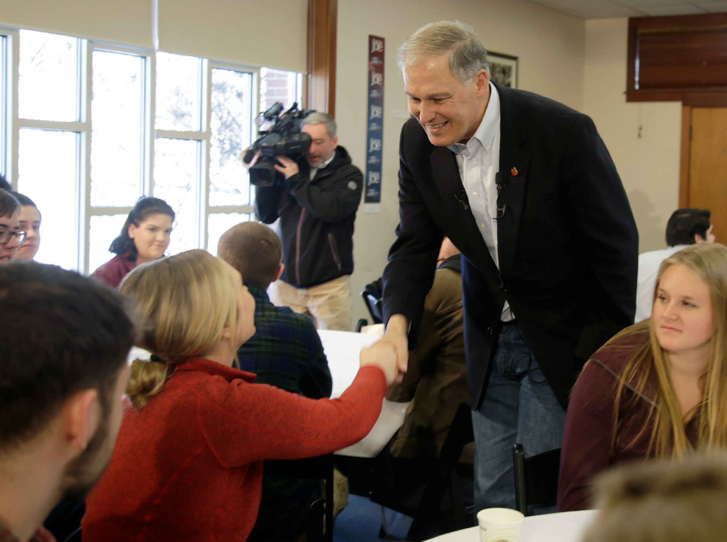 Washington Gov. Jay Inslee shakes hands with students after speaking at Saint Anselm College, Tuesday, Jan. 22, 2019, in Manchester, N.H.
