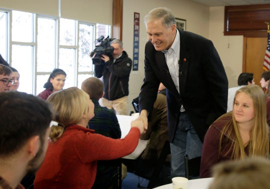 Gov. Jay Inslee shakes hands with students after speaking at Saint Anselm College on Tuesday in Manchester, N.H. Should Washington's governor decide to enter run for president, he'll face a crowded Democratic field.