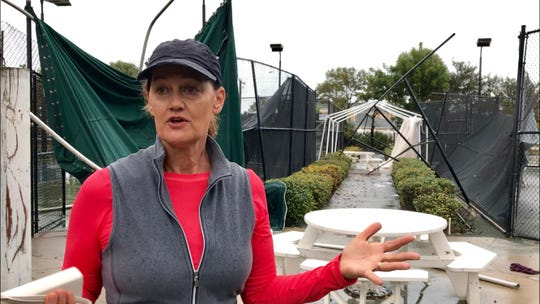 Kiwi Tennis Club General Manager Anna Stroman stands near damaged tennis courts Thursday morning.