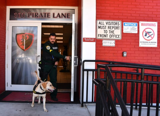 BCSO Cpl. Kirk Geweniger visits schools in the county with his Labrador, Sonic, who's trained to sniff out drugs. Here he leads Sonic through Palm Bay High.