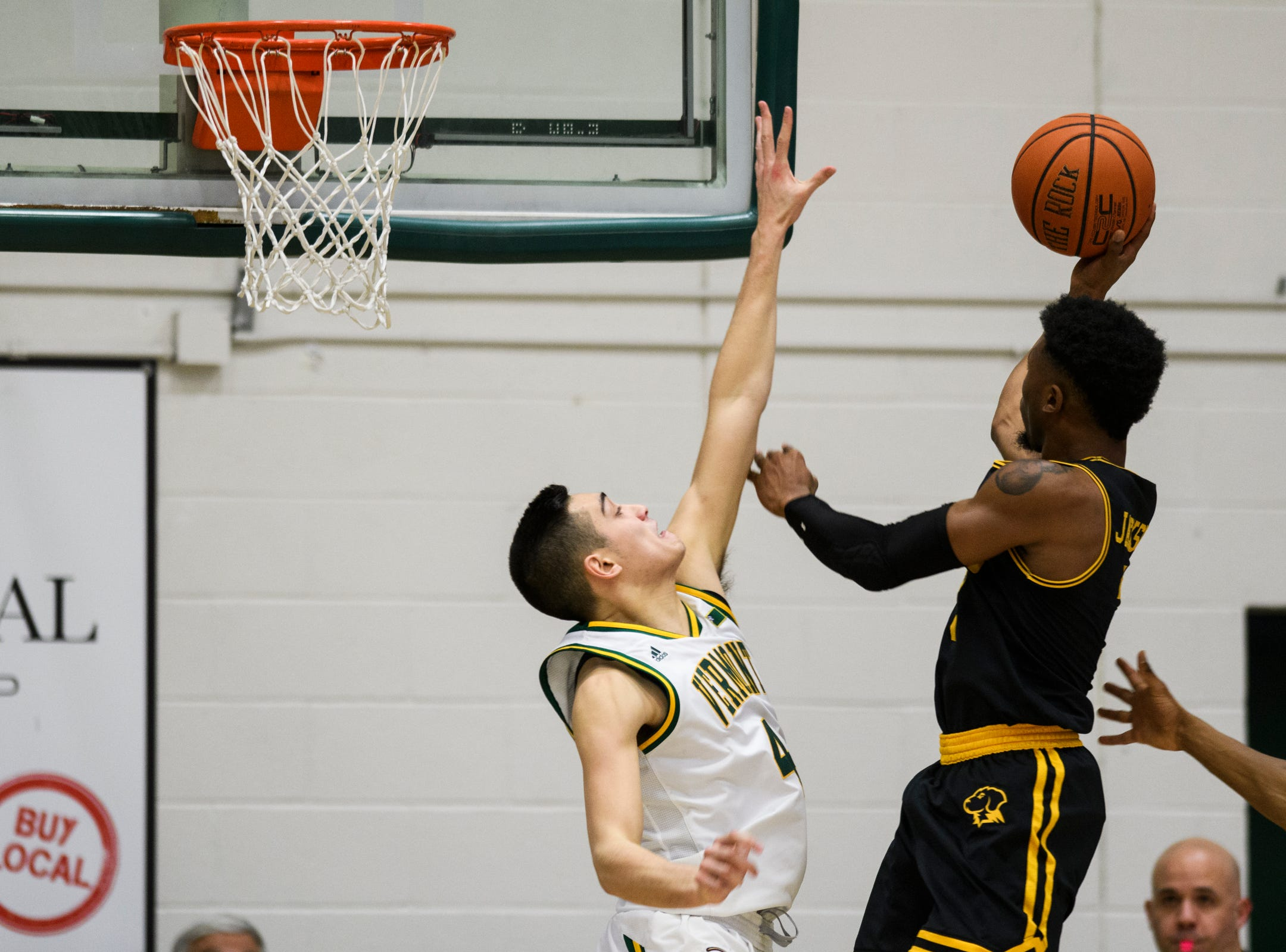 Vermont guard Robin Duncan (4) tries to block the shot by UMBC's K.J. Jackson (3) during the men's basketball game between the UMBC Retrievers and the Vermont Catamounts at Patrick Gym on Wednesday night January 23, 2019 in Burlington, Vermont.