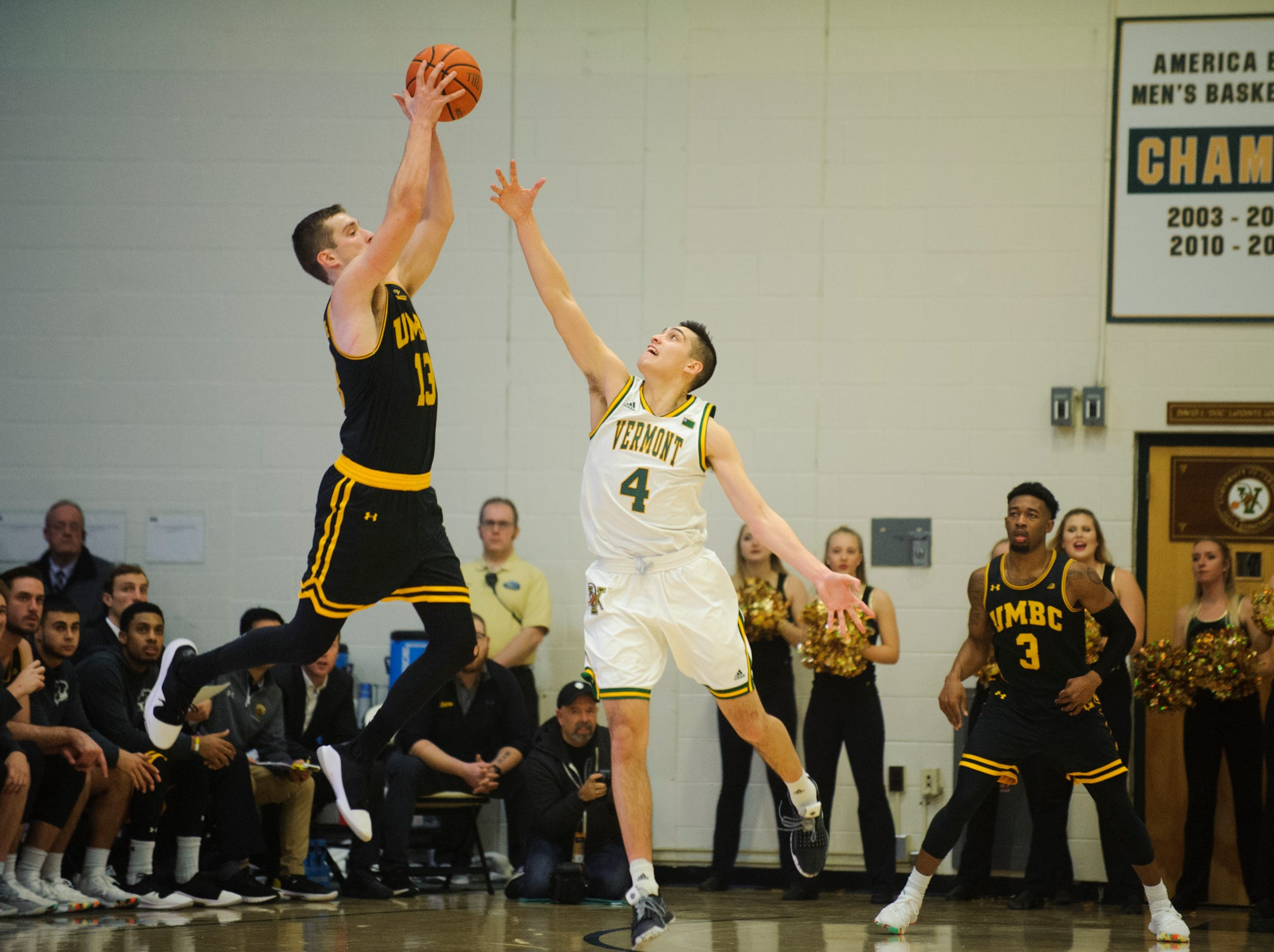 UMBC's Joe Sherburne (13) leaps to grab the ball over Vermont guard Robin Duncan (4) during the men's basketball game between the UMBC Retrievers and the Vermont Catamounts at Patrick Gym on Wednesday night January 23, 2019 in Burlington, Vermont. (