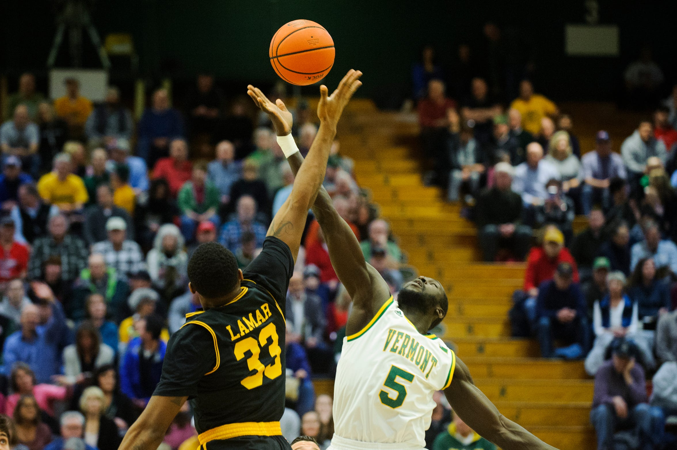 Vermont forward Samuel Dingba (5) and UMBC's Arkel Lamar (33) battle for the opening tip off during the men's basketball game between the UMBC Retrievers and the Vermont Catamounts at Patrick Gym on Wednesday night January 23, 2019 in Burlington, Vermont.