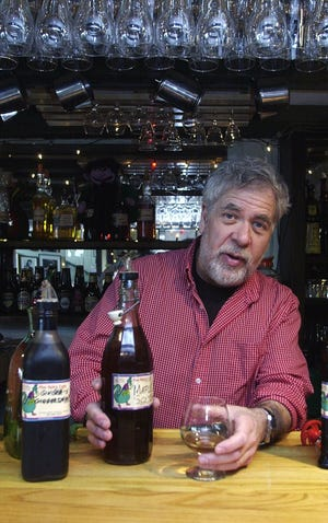 Jerry Weinberg, owner of Five Spice Cafe on Church Street in Burlington, pours a snifter of his own brand of maple scotch in 2001.