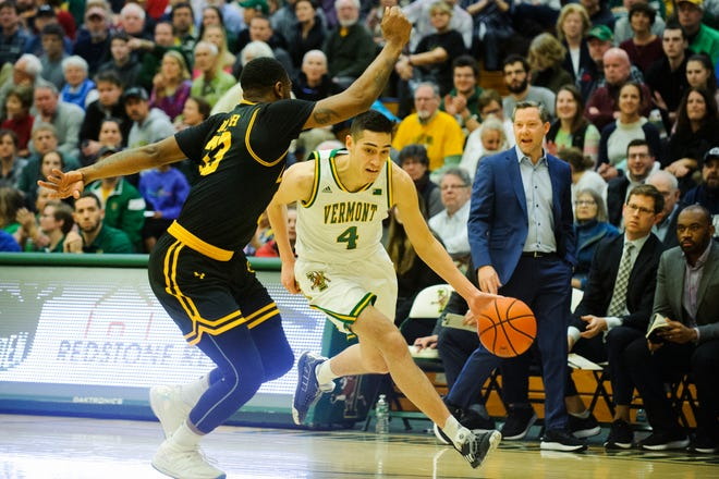 Vermont guard Robin Duncan (4) dries to the hoop past UMBC's Arkel Lamar (33) during the men's basketball game between the UMBC Retrievers and the Vermont Catamounts at Patrick Gym on Wednesday night January 23, 2019 in Burlington, Vermont.